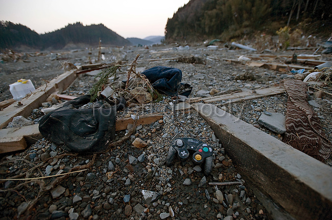 A game console lies among the debris after the mega-tsunami in Minami-Sanriku, a coastal town in Miyagi Prefecture, Japan on 14 March, 2011. Around 10,00 of the town's 17,000 population are reported as either dead or missing. Photographer: Robert Gilhooly