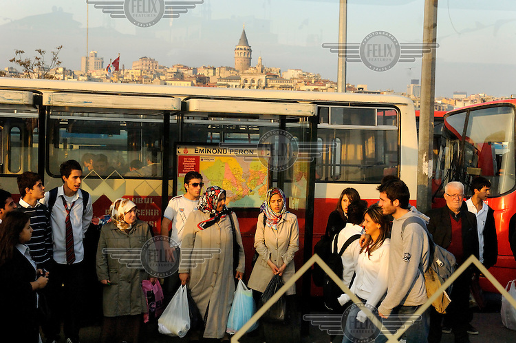 People waiting at an Eminonu bus station with Galata district visible behind.