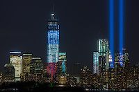 The twin beams of light of the Tribute in Light, an annual memorial to the events of September 11, 2001, shine into the evening sky in New York City over the skyline of lower Manhattan during testing on Monday, September 10, 2012.  This view of the skyline includes two symbols of freedom, the Statue of Liberty and the Freedom Tower (One World Trade Center), under construction at the site of the original Twin Towers.  The Freedom Tower, lighted in the red, white, and blue colors of the American flag, is scheduled for completion in 2013.