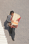 A man with rugs over his shoulder, walks through the market in Marrakesh, Morocco.