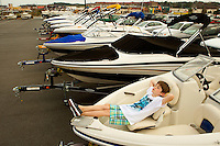 "Photography of Concord Mills Mall, a 1.4 million-square-foot mall located in Concord, NC, about 12 miles from Charlotte, NC. In this image, Robert Mullis, 9, from Fort Lawn, South Carolina, kicks back and relaxes in one of the many boats on display in the parking lot of Bass Pro Shops Outdoor World at Concord Mills.  Mullis said "" One day I will one of these of my own."" Photo is part of a photographic series of images featuring Concord, NC, by photographer Patrick Schneider."