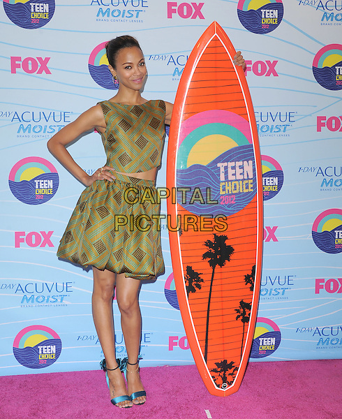 Zoe Saldana.Teen Choice Awards 2012 - Press Room held at Gibson Amphitheatre, Universal City, California, USA..July 22nd, 2012.full length dress surfboard brown yellow gold green sleeveless print hand on hip blue open toe ankle strap sandals shoes top skirt                                                                         .CAP/RKE/DVS.©DVS/RockinExposures/Capital Pictures.