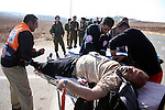 A wounded Palestinian man receives treatment by medics after clashes with Jewish settlers as he try to evacuate them from Palestinian land near the village of Yatta, south of the West Bank city of Hebron on Jan. 2, 2011. Photo by Najeh Hashlamoun