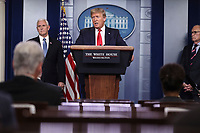 United States President Donald J. Trump speaks during a press conference with members of the coronavirus task force in the Brady Press Briefing Room of the White House on March 24, 2020 in Washington, DC. At left is US Vice President Mike Pence and at far right is Director of the National Economic Council Larry Kudlow.<br /> Credit: Oliver Contreras / Pool via CNP/AdMedia