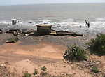 Rapid coastal erosion at East Lane, Bawdsey, Suffolk, England. Soft crag cliffs are easily eroded, dark underlying London clay is exposed. The second world war pill box indicates where the coast was around ten years ago.