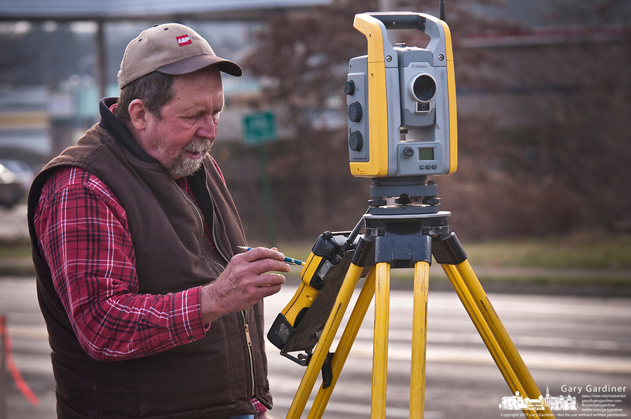 Surveyors mark locations and elevations along a city road as one of the early phases of deciding how best to rebuild the intersection and roadway leading to a nearby Interstate highwa.. Increased traffic along the road, the expansion of a nearby hospital, and more construction at a new business district built on farm land have begun to overload the intersection and roadway.