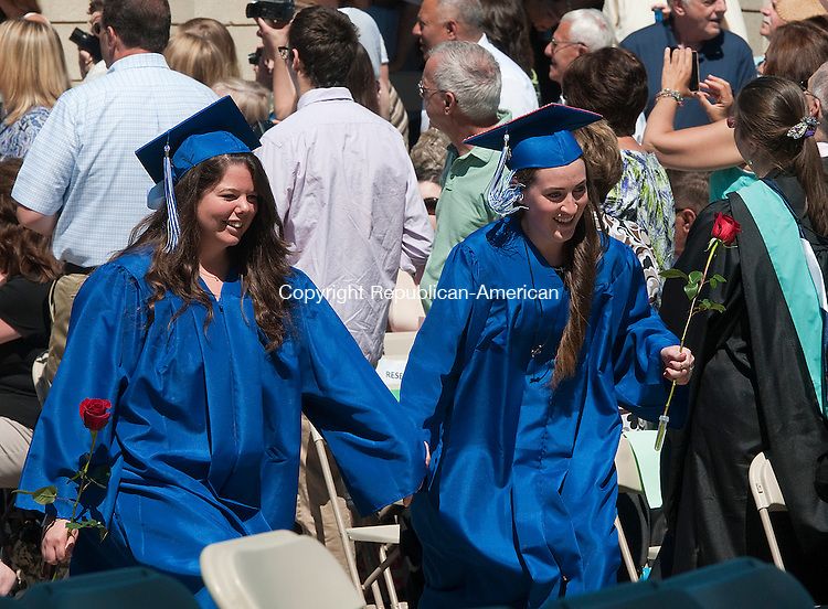 WOODBURY, CT-062114JS01--Nonnewaug High School graduates Maggie Disbrow and Carli Cioppa hold hands as they make they way to their seats during graduation ceremonies Saturday at the school in Woodbury.<br /> Jim Shannon Republican-American