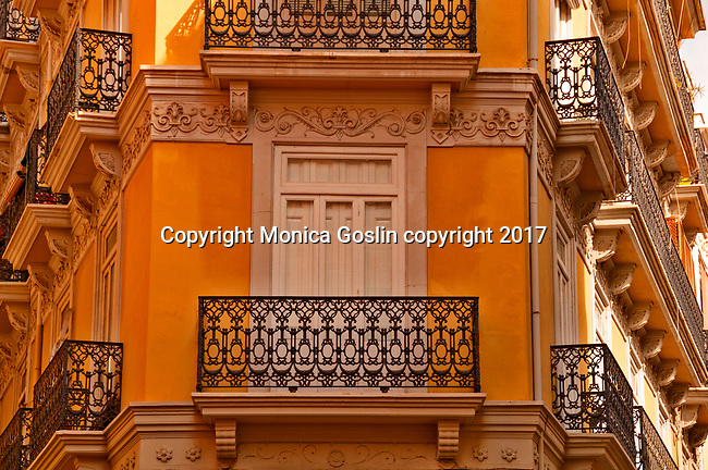 Iron balconies of a yellow building in Valencia, Spain