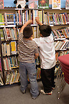 Oakland CA Latino 2nd graders picking out books in school library