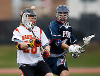 John Haus (26) of Maryland passes the ball away from  Julian Maldonado (4) of Penn at Ludwig Field in College Park, Maryland.