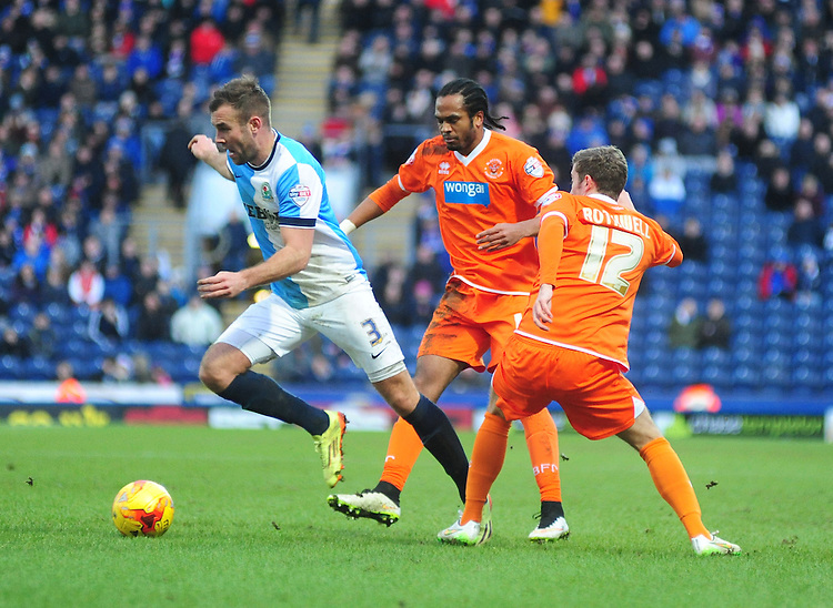 Blackburn Rovers' Tommy Spurr gets past Blackpool's Charles Dunne (left) and Blackpool's Joe Rothwell (right)<br /> <br /> Photographer Andrew Vaughan/CameraSport<br /> <br /> Football - The Football League Sky Bet Championship - Blackburn Rovers v Blackpool - Saturday 21st February 2015 - Ewood Park - Blackburn<br /> <br /> &copy; CameraSport - 43 Linden Ave. Countesthorpe. Leicester. England. LE8 5PG - Tel: +44 (0) 116 277 4147 - admin@camerasport.com - www.camerasport.com