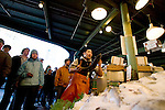 A fish monger at Pike Place Fish Company throws a purchased fish to be wrapped at Pike Place Market in Seattle.  For over a century a century, the Pike Place Market, has become a city institution and a national attraction, bringing in over a million tourists a year. .Jim Bryant Photo. ©2010. ALL RIGHTS RESERVED.