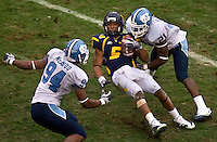 West Virginia quarterback Pat White (5) is tackled by North Carolina linebacker Brian White (94) and Da'Norris Searcy (21) during the Meineke Car Care Bowl college football game at Bank of America Stadium in Charlotte, NC.