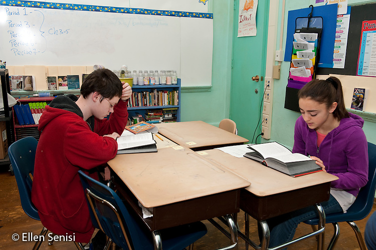 MR / Schenectady, New York. Oneida Middle School (urban public school). 8th grade English class. Students (boy; 13, and girl; 13) read the same book during classroom silent reading time. MR: Ald1, Ott2. ID: AJ-g8b. © Ellen B. Senisi