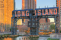 Gantry cranes stand in Gantry Plaza State Park in Long Island City, Queens, New York in the warm light of late afternoon.  The restored cranes, dating from 1920, were used to load Long Island Railroad rail car floats with industrial goods.