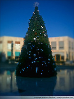 Iphone photo with tilt shift app of Christmas tree in fountain at a suburban mall.