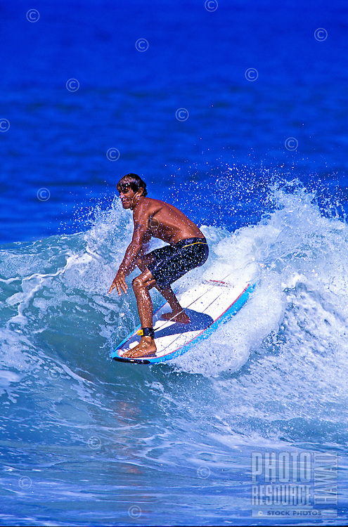 A tanned young surfer rides a choppy white wave at a Maui beach.