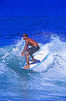 A tanned young surfer rides a choppy white wave at a Maui beach.