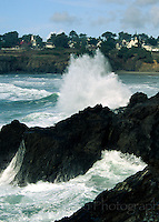Wave crashing on rocks with view of Mendocino, CA.  Drum scan from 35mm film.. © John Birchard