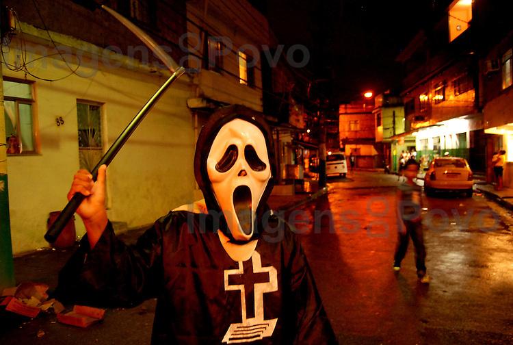 Jovem fantasiado de morte no carnaval, pelas ruas da  Baixa do Sapateiro, Conjunto de favelas da Maré, Rio de Janeiro, Brasil.
