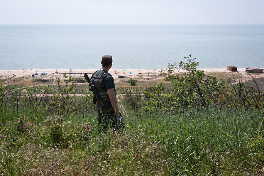 UKRAINE: Sherokyne frontline, a soldier of the Donbass battalion is looking at Shyrokyne beach that was a holiday place before. <br /> <br /> UKRAINE: Front de Shyrokyne, un soldat du bataillon Donbass regarde vers la plage Shyrokyne qui &eacute;tait un lieu de vacances auparavant.