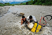Contraband smugglers, carrying gasoline barrels on a bicycle, fall down into the river Tachira on the Colombia-Venezuela border, 3 May 2006. Venezuelan gasoline, being 20 times cheaper than in Colombia, is the most wanted smuggling item, followed by food and car parts, while reputable Colombian clothing flow to Venezuela. There are about 25,000 barrels of gasoline crossing illegally the Venezuelan border every day. The risky contraband smuggling, especially during the rainy season when the river rises, makes a living to hundreds of poor families in communities on both sides of the frontier.