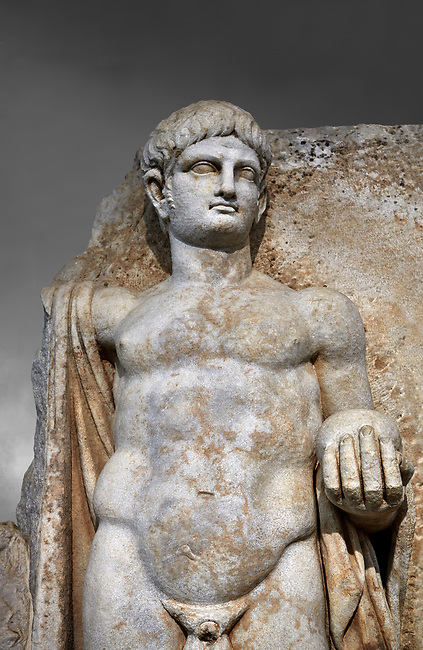 Detail of a Roman Sebasteion relief  sculpture of Emperor Nero with captive, Aphrodisias Museum, Aphrodisias, Turkey.  Against a grey background.<br /> <br /> Naked warrior emperor Nero holds the orb of world rule in one hand and crowns the military trophy with the other. Between the trophy and the emperor stands a bound captive boy. He wears long barbarian trousers and looks up at Nero.