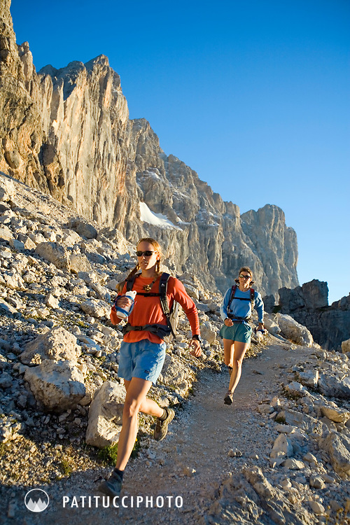 Two women trail running the Dolomite's Alta Via 1. The trail they are on is directly beneath the Civetta, one of the Dolomite's tallest walls. The Alta Via One is one of Italy's most famous trails