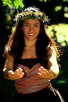 Smiling Hawaiian hula dancer in a park in Honolulu on Oahu, dancing kahiko hula