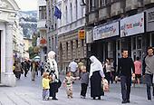 Sarajevo, Bosnia and Herzegovina. People walking on the street; muslim women with children; EU flag; Centrotrans travel agency; Swissair.