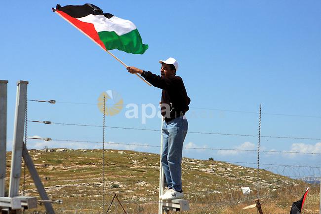 Palestinian protester waves his national flag during a demonstration marking Land Day and protesting against Israel's separation barrier, in the West Bank village of Budrus, near Ramallah, Tuesday, March 30, 2010. Land Day commemorates the killing of six Arab citizens of Israel by the Israeli army and police on March 30, 1976 during protests over Israeli confiscations of Arab land. Photo by Issam Rimawi