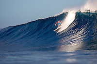A surfer rides a wave at Backdoor Pipeline on O'ahu.