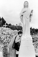 Bosnia. Medjugorje. Podbrdo, also called the Apparition Hill, is the place above the village of Bijakovici near Medjugorje where the six visonaries in the first days saw the Virgin Mary. Since then it is here that the pilgrims gather for prayer of the rosary. On september 8 2001by a gift of koreans pilgrims, a statue of the Queen of Peace, the Virgin Mary, was erected and blessed at this place. A pilgrim kisses the feet of the Virgin Mary.© 2002 Didier Ruef