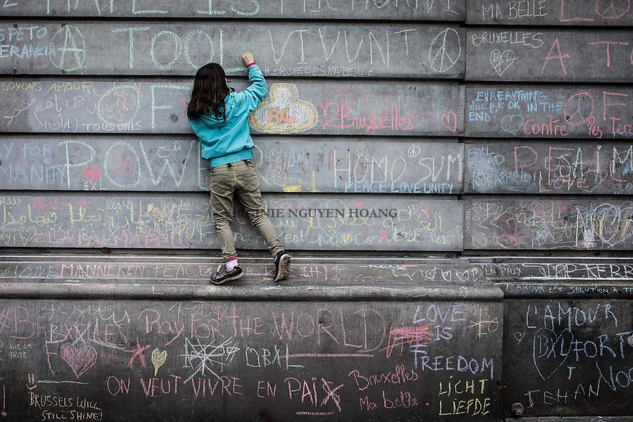 BRUXELLES, Belgique: Une petite fille desssine sur les murs de la Bourse où sont écris des milliers de messages pour les victimes des attentats,  le 23 mars 2016. 31 personnes sont mortes et 300 ont été blessées dans les attentats commis à Zaventem et dans la station du métro bruxellois Maelbeek, selon le dernier bilan du Centre de crise.Dans le centre de Bruxelles, des centaines de personnes se rassemblent en commemoration aux victimes.