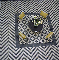 Aerial view of a table and chairs in the courtyard with a striking black and white geometric tiled floor
