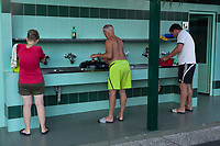 Switzerland. Canton Ticino. Tenero. Camping Campofelice. A woman and two men wash kitchen plates in public facilities. 21.07.2018 © 2018 Didier Ruef