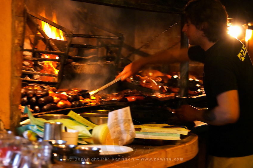 The restaurant kitchen with a big grill barbecue where all sorts of pork beef and chicken meat and sausages are grilled. The chef cook working with a long grilling fork. at the restaurant La Estacada on the waterside Montevideo, Uruguay, South America