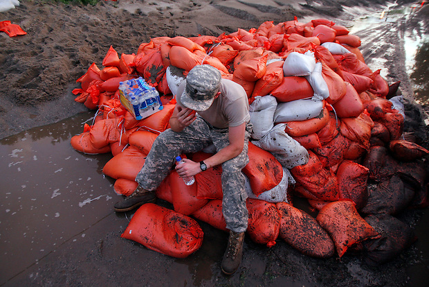 Iowa National Guardsman Spc. Dustin Houghton takes a break atop a pile of sandbags adjacent to the Birdland levee Thursday evening, June 12, 2008 in Des Moines.  He is one of about 300 guard members helping to raise the levee in anticipation of high flood water from the nearby Des Moines River.