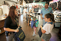 NWA Democrat-Gazette/DAVID GOTTSCHALK Corporal Tiffney (cq) Lindley speaks with Keith Knox and his daughters Micah (left), 6, and Molly (right), 10, during the Fayetteville Police Department Coffee with a Cop event at Rick's Bakery in Fayetteville. Members of the department, including Chief of Police Greg Tabor, were on hand to visit with members of the community to answer questions, listen to concerns and get to know the officers. Free coffee and a donuts sprinkle bar were available.
