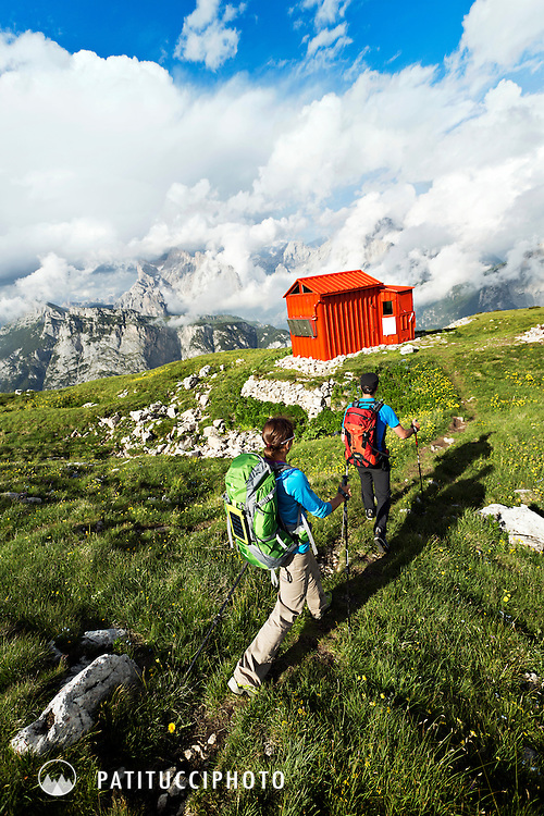 Couple trekking in the Italian Dolomites arriving to a small bivouac hut, the Bedin, in the Agordo region of the Dolomites