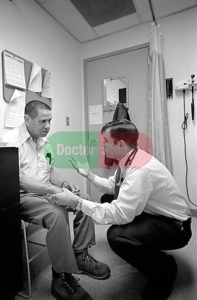 Male doctor examines hands and discusses condition with seated elderly male patient in examination room