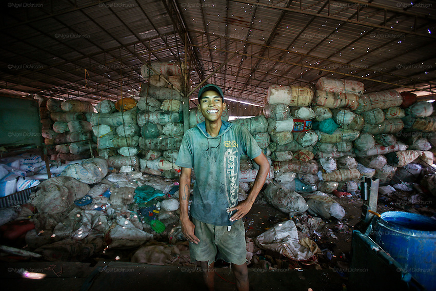A recycling factory worker smiles in the heat. Tons of sorted plastic standfs behind him. Recycling warehouse for plastics. The plastics are sorted by recycling workers earning less than a dollar day. They throw platsic of different textures and colours into various buckets. These are collected and placed into larger sacks. The plastic is then put through a mincer (like making minced meat for hamburgers) and the small crushed picese of plastic mixed with water in the process are then dried on mats in the sun, like for coffee beans. The dry plastic shavings are bagged and shipped off for export to Thailand and Vietnam