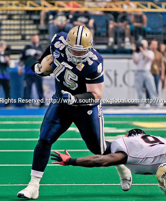 Aug 14, 2010: Tampa Bay Storm offensive lineman Thomas Kaleita rumbles forward with the ball as Orlando Predator linebacker James Bryant (#24) tries to bring him down.  The Storm defeated the Predators 63-62 to win the division title at the St. Petersburg Times Forum in Tampa, Florida. (Mandatory Credit:  Margaret Bowles)