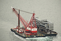Aerial of large derrick and mechanized cruise ship gangway in tow