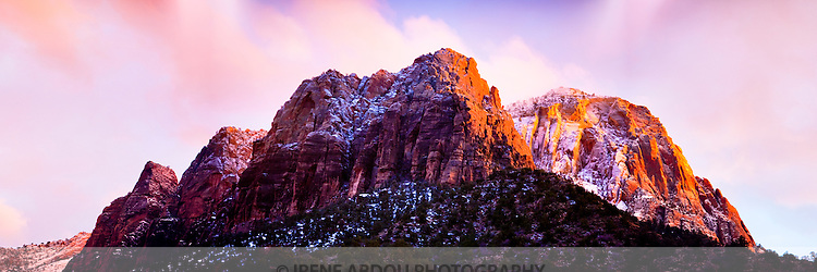 Wet from a recent snowstorm, the peaks of the Zion Mountains glow in fiery colors of orange and yellow in the last sunset light.