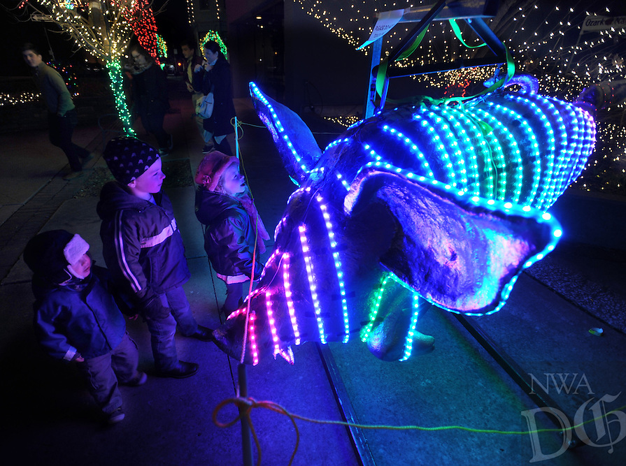 NWA Democrat-Gazette/ANDY SHUPE<br /> Nathan Gibson, 2; (from left) Elliot Gibson, 6; and Addie Gibson, 5; all from Denver, inspect a pig wrapped in lights Thursday, Dec. 31, 2015, that is used to ring in the new year during the fifth annual Last Night Fayetteville celebration on the town's square. The celebration featured music and performances for all ages on 11 stages leading up to the Hog Drop and fireworks at midnight. Visit nwadg.com/photos to see more photographs from the event.