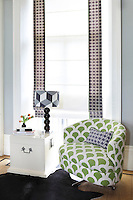 A light green, patterned armchair dressed with a purple scatter cushion echoed in the bands of matching fabric on the blind behind