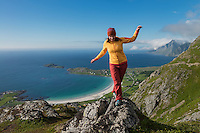 Female hiker walks across rocks on summit of Nubben, Ramberg, Flakstadøy, Lofoten Islands, Norway