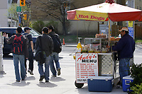 Toronto (ON) CANADA,  April , 2008-..Student of various ethnic origin walk  beside a hot dog standon College street  between  University of Ontario buildings...