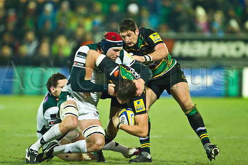 Tom Wood is tackled by Nick Kennedy. James Downey (right) and Ryan Lamb (left) lend support.  Northampton Saints v London Irish, Aviva Premiership, 26 November 2010 at Franklin's Gardens.  Final score: Northampton Saints 35-23 London Irish.